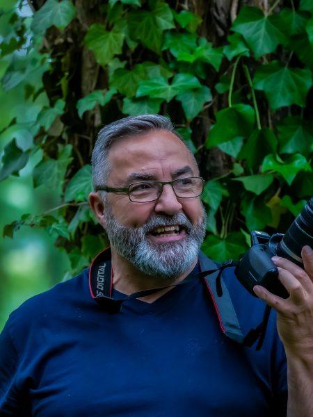 Karl-Heinz Fischer mit Kamera vor einem mit Efeu bewachsenen Baum